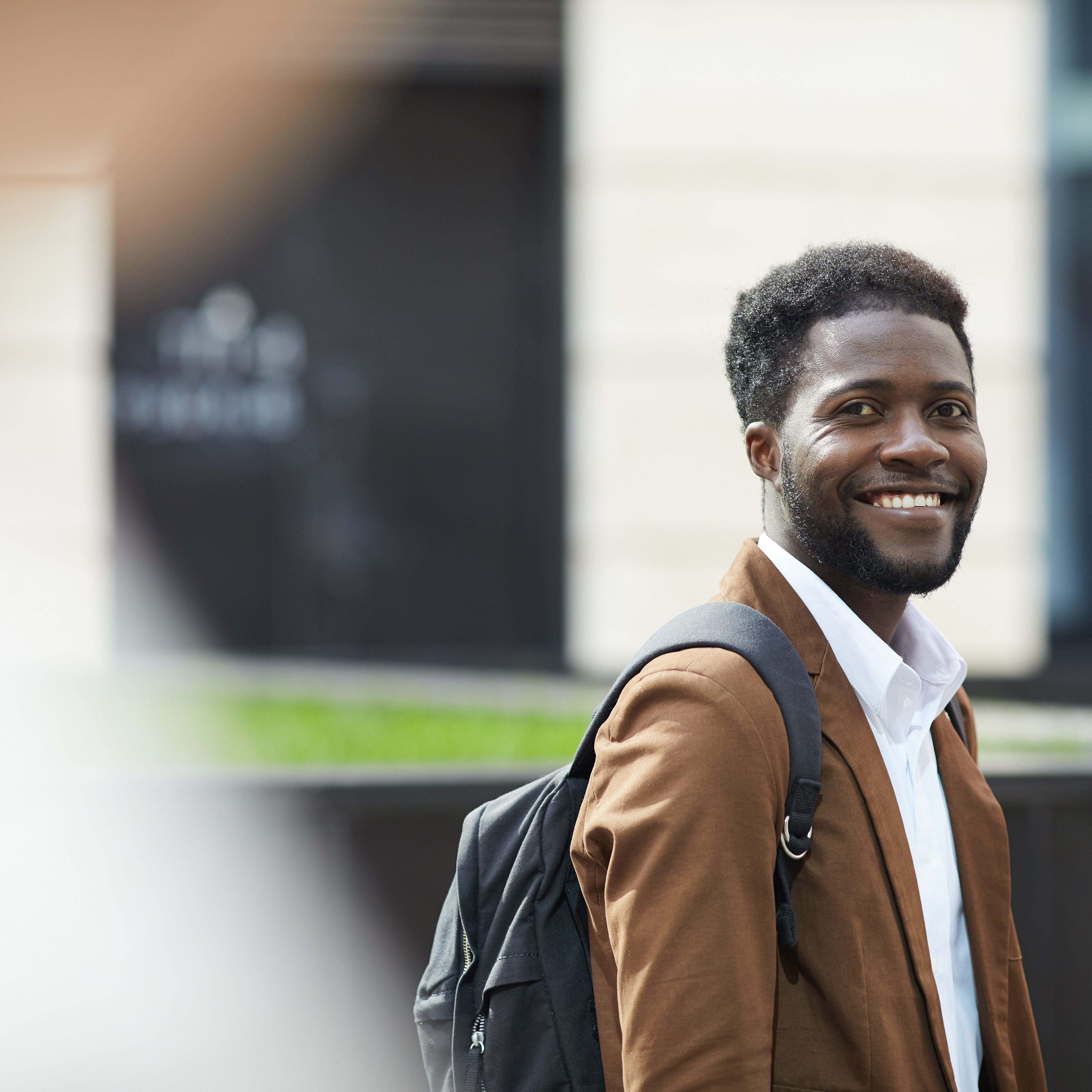 Waist up portrait of young African-American man smiling happily at camera while standing outdoors ion city street, copy space
